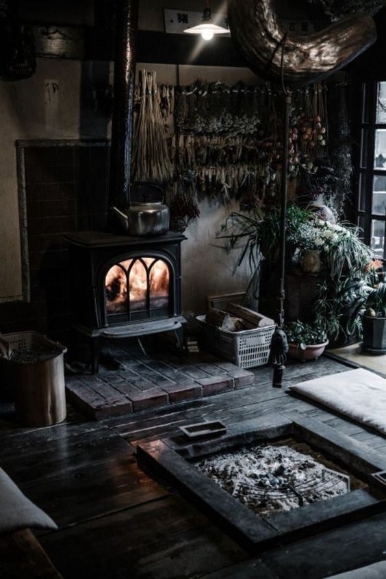 a rustic Gothic space with a vintage hearth, a firepit, potted plants, and black floors for a witch-like feel