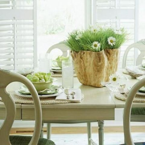a rustic spring tablescape with woven chargers, green porcelain, a catchy wooden planter and white blooms