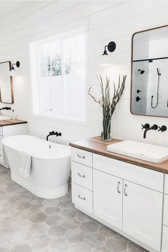 a serene farmhouse bathroom with a white vanity, a wooden countertop, an oval tub, mirrors in sleek frames