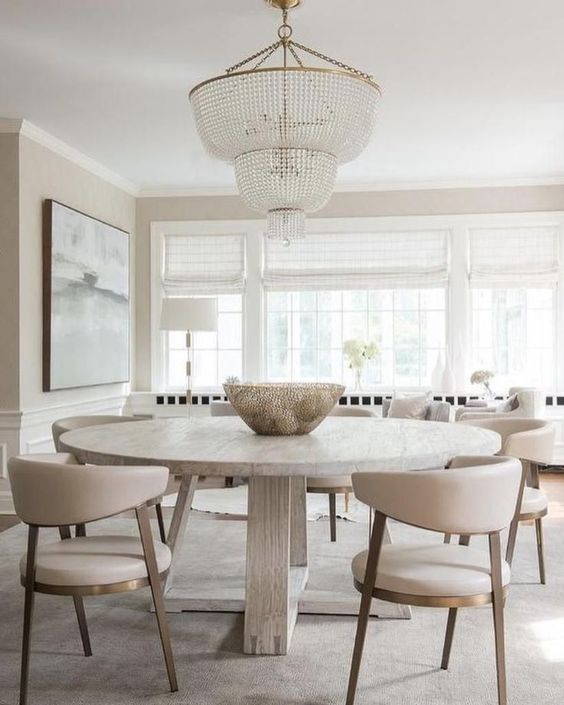 a serene neutral dining room with a round table, neutral chairs, an oversized crystal chandelier and a beautiful artwork
