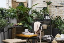 a smal boho terrace with metal furniture, a wooden table, potted greenery, lights and a wooden screen