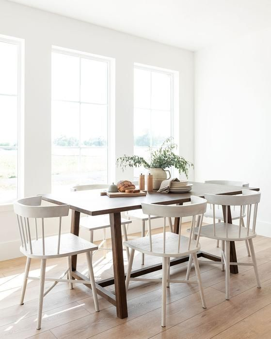 a small airy dining room with a stained table and vintage white chairs, some greenery is a very welcoming and cool space