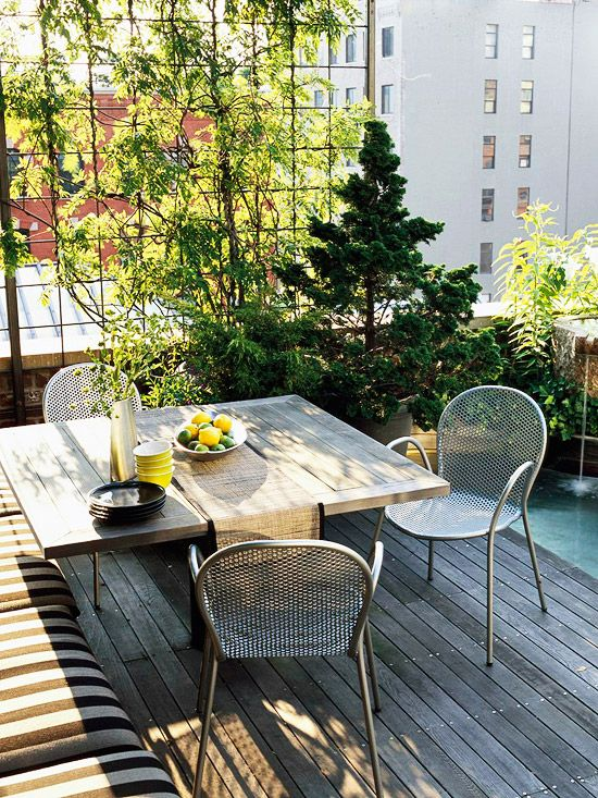 a small and cozy terrace with an upholstered bench, a wooden table, metal chairs and a mini garden in pots