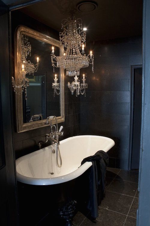 a small and exquisite Gothic bathroom with matte black tiles and a grey tile floor, a vintage black and white tub, a mirror in a gilded frame and a crystal chandelier
