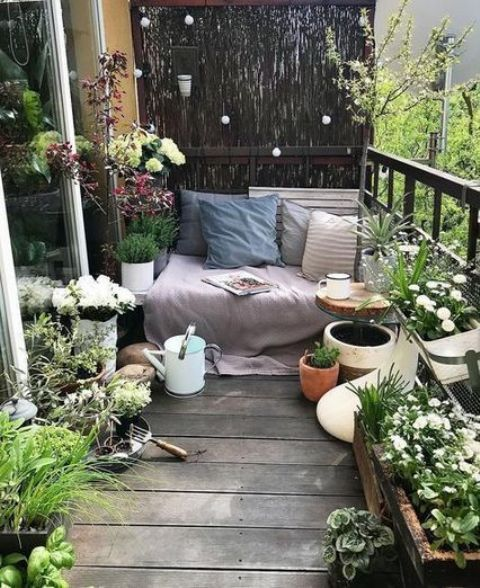 a small and fresh terrace with potted greenery and blooms, a bench with blankets and pillows plus a watering can