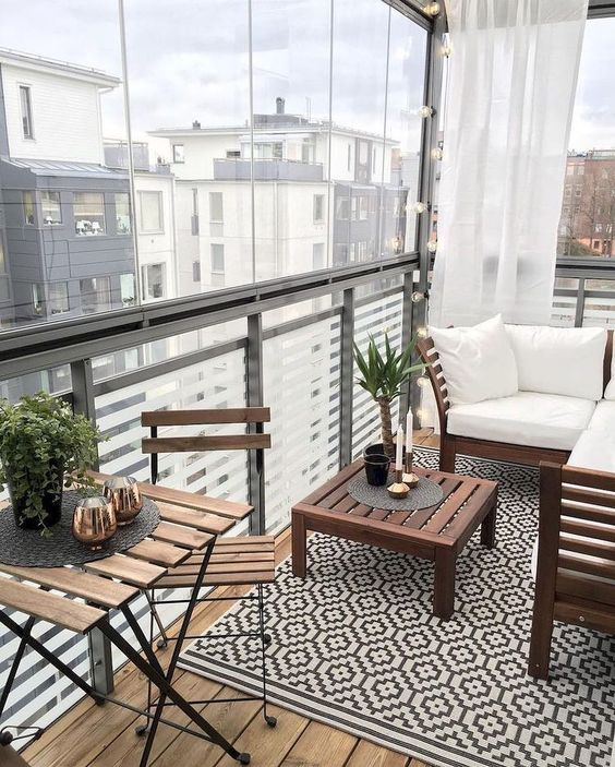 a small contemporary balcony with a geo rug, simple stained furniture and some greenery