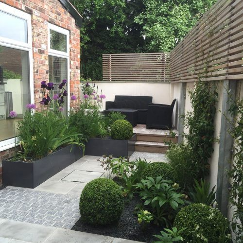 a small contemporary terrace with dark furniture, potted greenery and blooms and wooden screens for privacy
