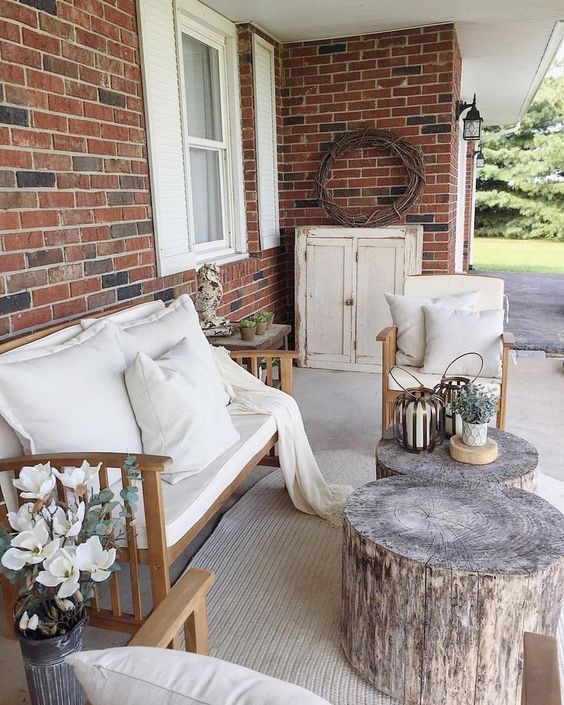 a small farmhouse terrace with neutrla upholstered furniture, tree stumps as side table and potted greenery and blooms