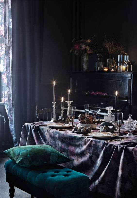 a sophisticated dining room with black walls, a black piano, vintage chairs, an emerald bench, candles and floral linens