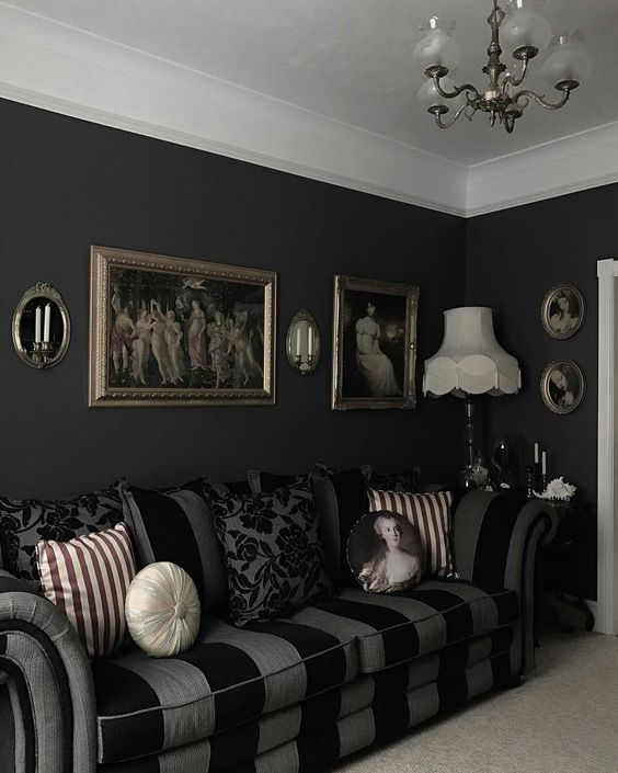 a stylish Gothic living room with black walls, a striped sofa, artworks, a chandelier and printed pillows