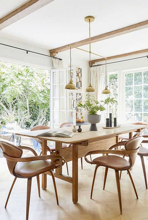 a stylish dining room with a stained wooden table, leather and wood chairs, a cool pendant lamp and beams on the ceiling