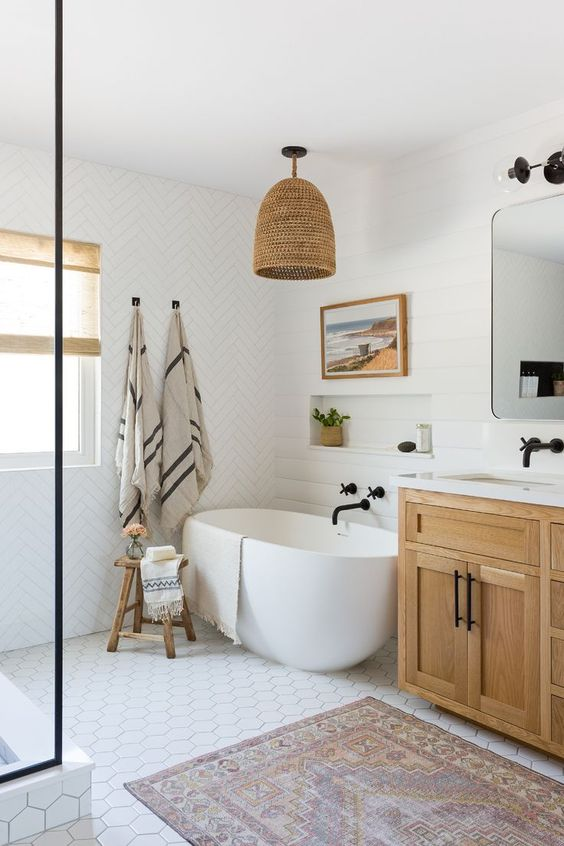 a stylish farmhouse bathroom with mismatching white tiles, a wooden vanity, a woven lamp, an oval tub and black fixtures for a modern feel