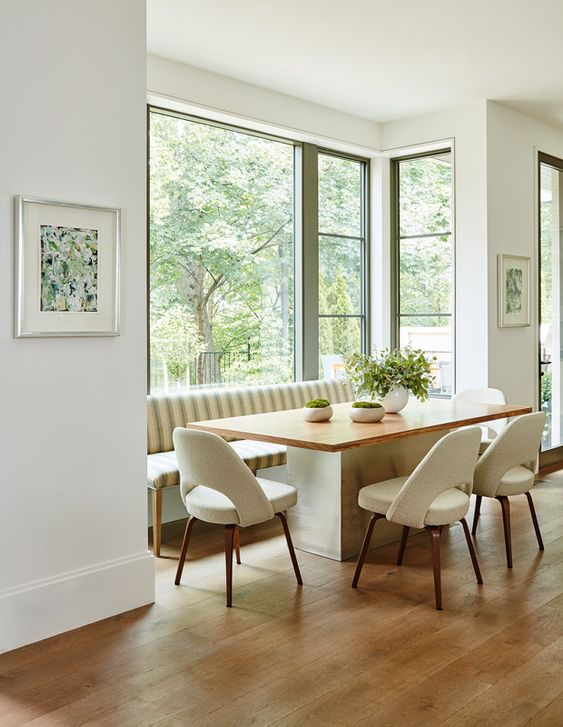 a stylish mid-century modern dining space by the window, with a large striped sofa, a table and creamy chairs and a gorgeous view