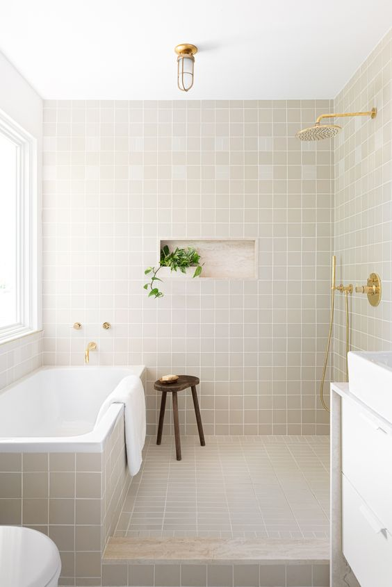 a stylish modern bathroom clad with square grey tiles, a bathtub clad with them, too, a white vanity with a white sink and gold touches