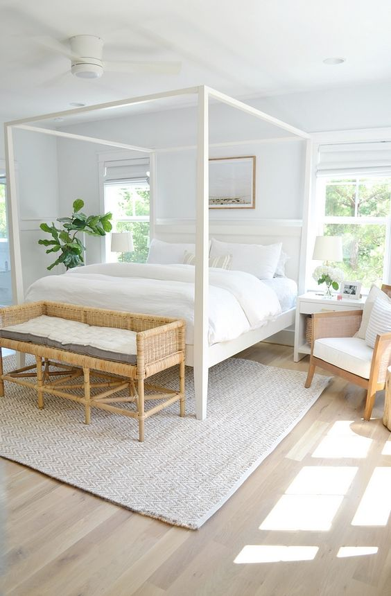 a stylish modern neutral bedroom with a white canopy bed, a woven bench, chairs and neutral textiles