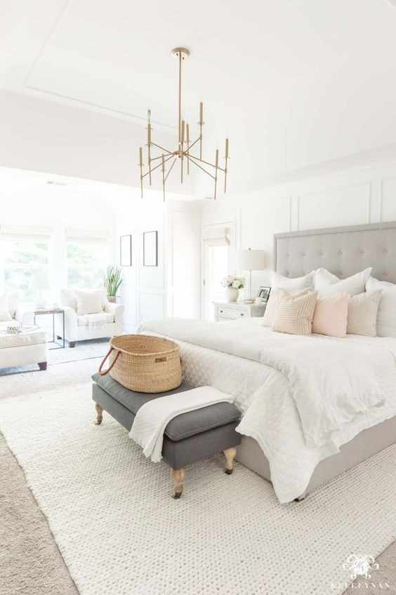 a stylish neutral bedroom with a grey upholstered bed, a brass chandelier, a grey bench, white chairs and pillows