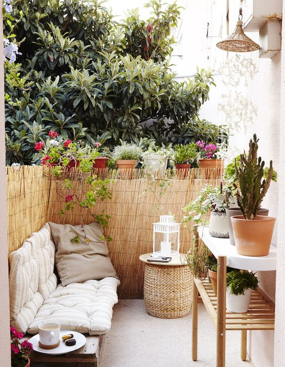 a tiny boho terrace with an upholstered bench, a wicker ottoman, a large plant stand and lots of potted plants around