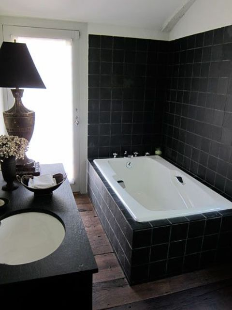 a very laconic Gothic bathroom clad with matte black tiles and a tub clad with them, a black vanity, a chic table lamp and white appliances