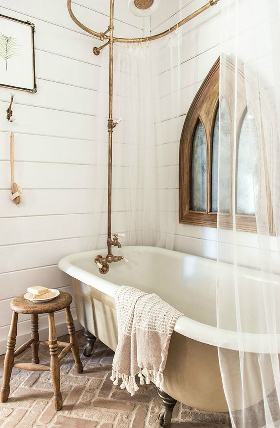 a vintage farmhouse bathroom with beadboard on the walls, a tan vintage tub, a wooden sotol, brass touches and a mirror in a wooden frame