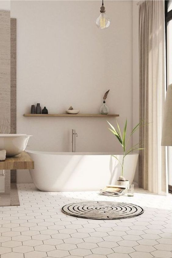 a warm contemporary bathroom with a hex tile floor, an oval tub, a floating vanity, a floating shelf and a round rug
