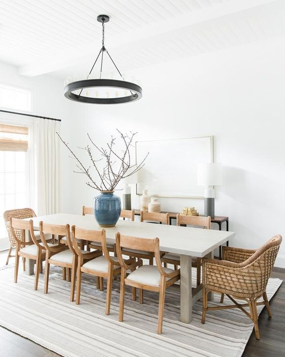 a welcoming modern farmhouse dining room with a console, a pendant black lamp, a long table, wooden and woven chairs