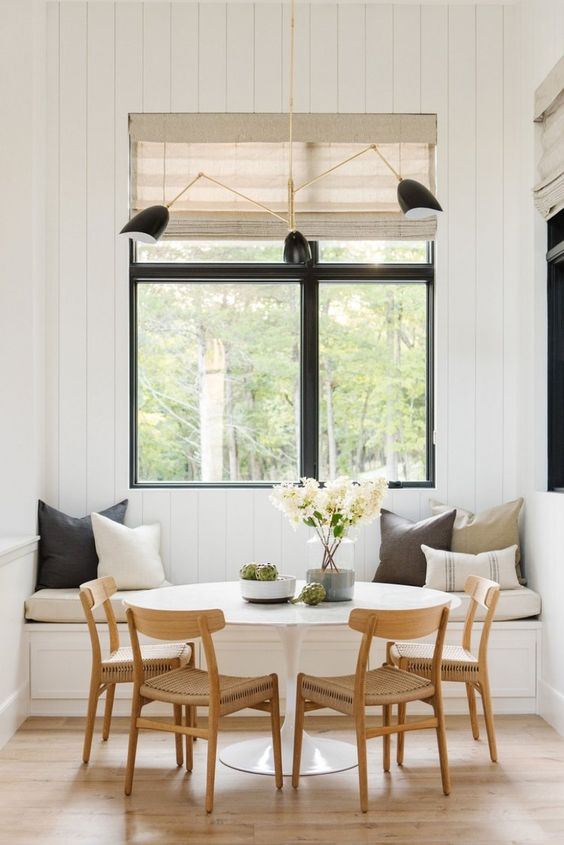 a welcoming modern farmhouse dining space with a built-in bench, a round table, woven chairs, touches of black and woven shades