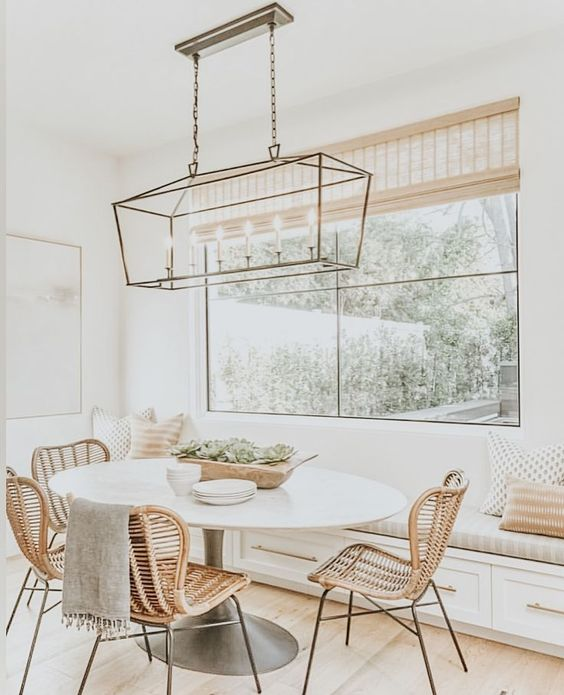 a welcoming modern farmhouse neutral dining space with a built-in bench, an oval table, rattan chairs, a chic brass pendant lamp