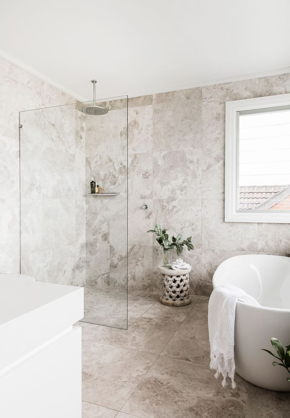 a welcoming neutral bathroom with catchy stone tiles, white appliances and a vanity and some greenery in vases