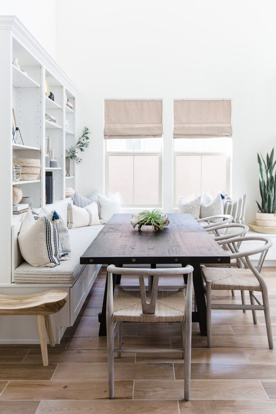 a welcoming neutral dining space with a built-in bench, a dark stained table, woven chairs and cool shades is very welcoming