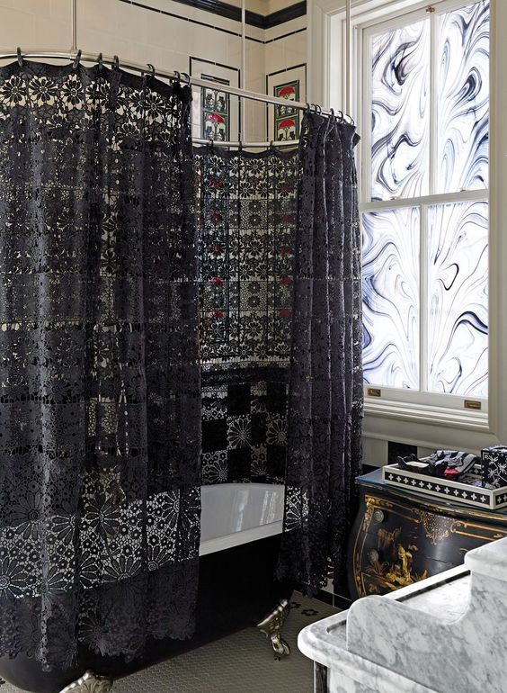 a whimsy Gothic bathroom with black and white mosaic tiles, a black vintage bathtub and a black lace curtain, marble glass and a marble vanity