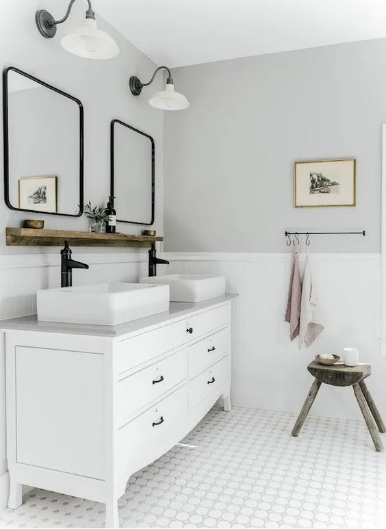 a white and grey farmhouse bathroom with panels, a white vanity and sinks, curved mirrors in black frames and sconces