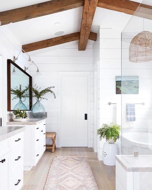 a white coastal bathroom with stained beams on the ceiling, white vanities, a bathtub and a shower space plus a large mirror