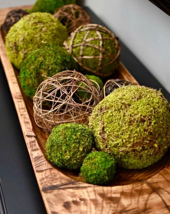 a wooden bowl with vine balls and moss ones is s stylish centerpiece or decoration for spring