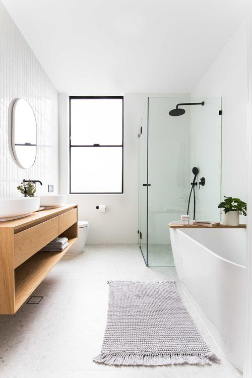 an airy contemporary bathroom with a floating vanity, an oval tub, a glass enclosed shower space and black fixtures