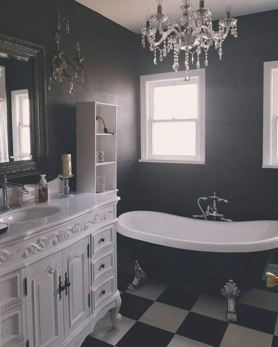 an elegant Gothic bathroom with a black and white tiled floor, a vintage white vanity, a black vintage bathtub, a crystal chandelier and a mirror in a lovely frame