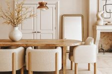 an elegant and chic neutral dining room with a stained table, neutral chairs, a fireplace clad with brick, a floor mirror and a very stylish pendant lamp