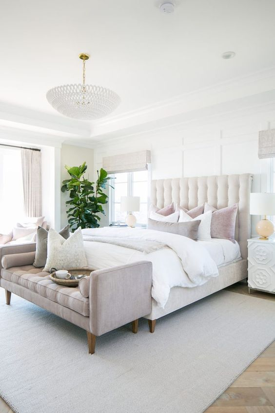 an elegant neutral bedroom with a creamy bed, neutral and pastel bedding, a pastel bench and a statement plant
