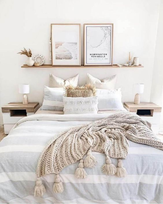 an ethereal neutral bedroom with wooden nightstands, a bed, an open shelf, pampas grass and artworks