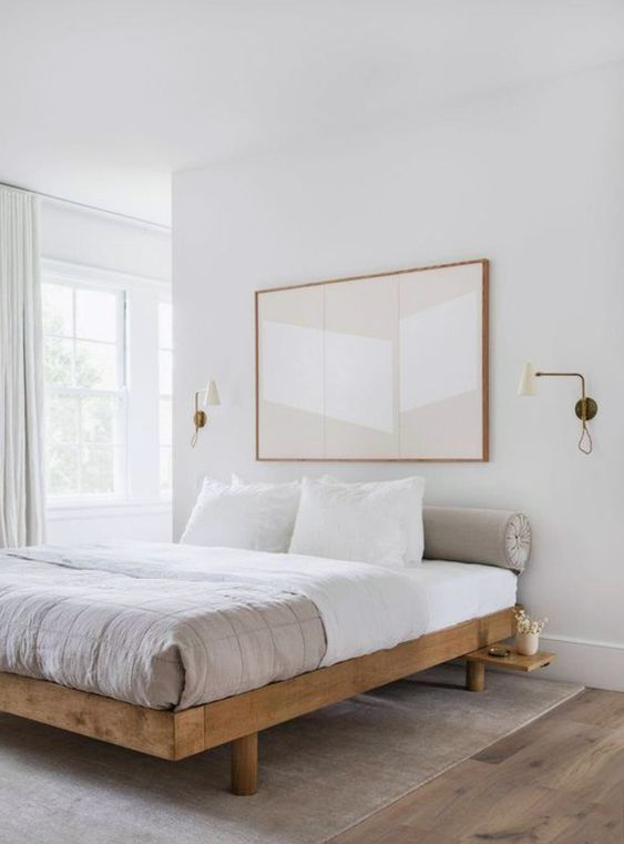 an etherel neutral bedroom with a wooden bed, neutral bedding and an oversized artwork plus sconces