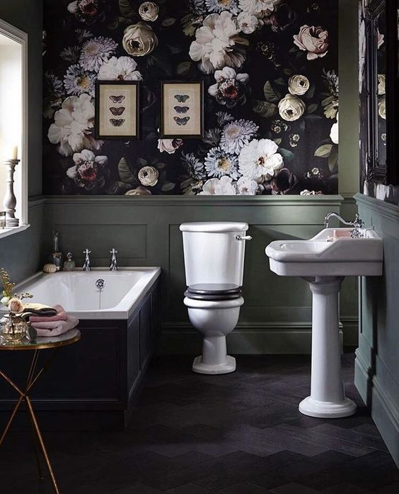 an exquisite Gothic bathroom with dark floral wallpaper and green panels, a tub with black panels, white appliances, a chic table and butterfly art