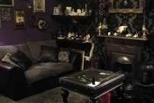 an exquisite living room with printed wallpaper, a mini fireplace, black furniture, open shelves with creative objects and a gallery wall
