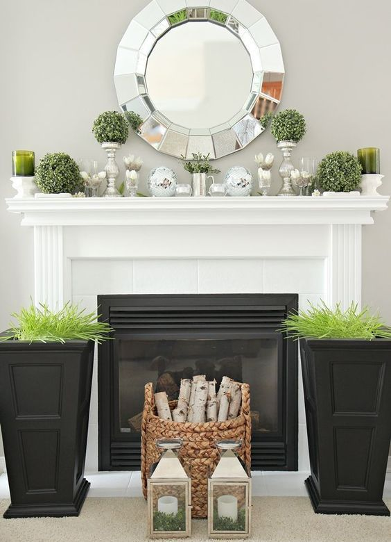 tall black planters with wheatgrass, a basket with firewood, greenery topiaries on stands and mercury glass candleholders