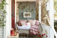 vintage inspired compact front porch with a seeting area and wine-colored front door