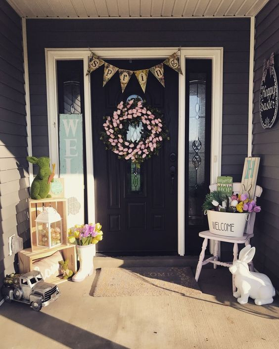 Easter porch decor with bunnies of moss and plastic, with colorful tulips, a tulip wreath and a bunting