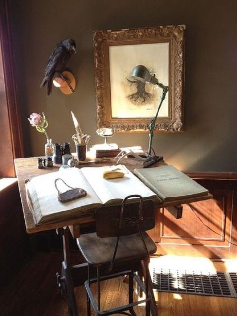 a Gothic Victorian home office with grey walls with paneling, a small desk and a vintage stool, a statement artwork, a raven and a retro metal desk lamp