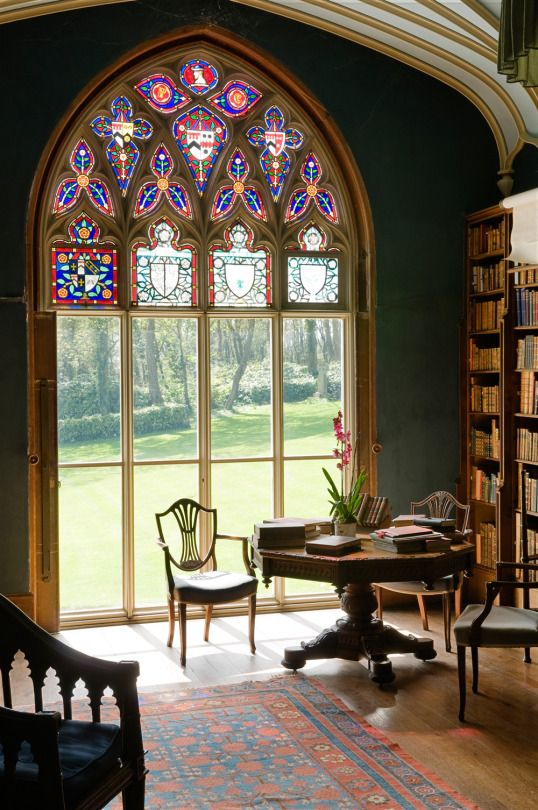 a Gothic-styled home office with an arched mosaic window, dark stained heavy furniture, a large bookcase is a stylish space