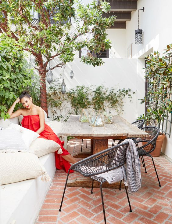 a Moroccan terrace styled for spring, with lots of greenery, potted greenery and trees and a large table and chairs