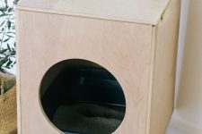 a Scandinavian cat litter box cover of plywood, with a round entrance and on legs can double as a side table