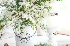 a basket tray with potted greenery, a vase with white blooming branches is a lush spring decoration