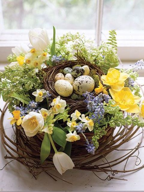 a beautiful blooming spring centerpiece of a nest with tulips, daffodils, hyacinths and fake eggs and moss
